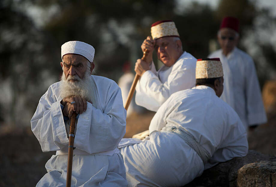 Members of the ancient Samaritan community gather during a pilgrimage marking the Sukkot holiday, known as the Feast of the Tabernacles, at the religion's holiest site on Mount Gerizim, near the West Bank town of Nablus, early Wednesday, Oct. 8, 2014. According to tradition, the Samaritans are descendants of Jews who were not deported when the Assyrians conquered the area in the 8th century B.C. Of the small community of close to 700 people, who adhere to Samaritanism, an Abrahamic religion closely related to Judaism, half live in a village at Mount Gerizim, and the rest in the city of Holon near Tel Aviv. (AP Photo/Majdi Mohammed)