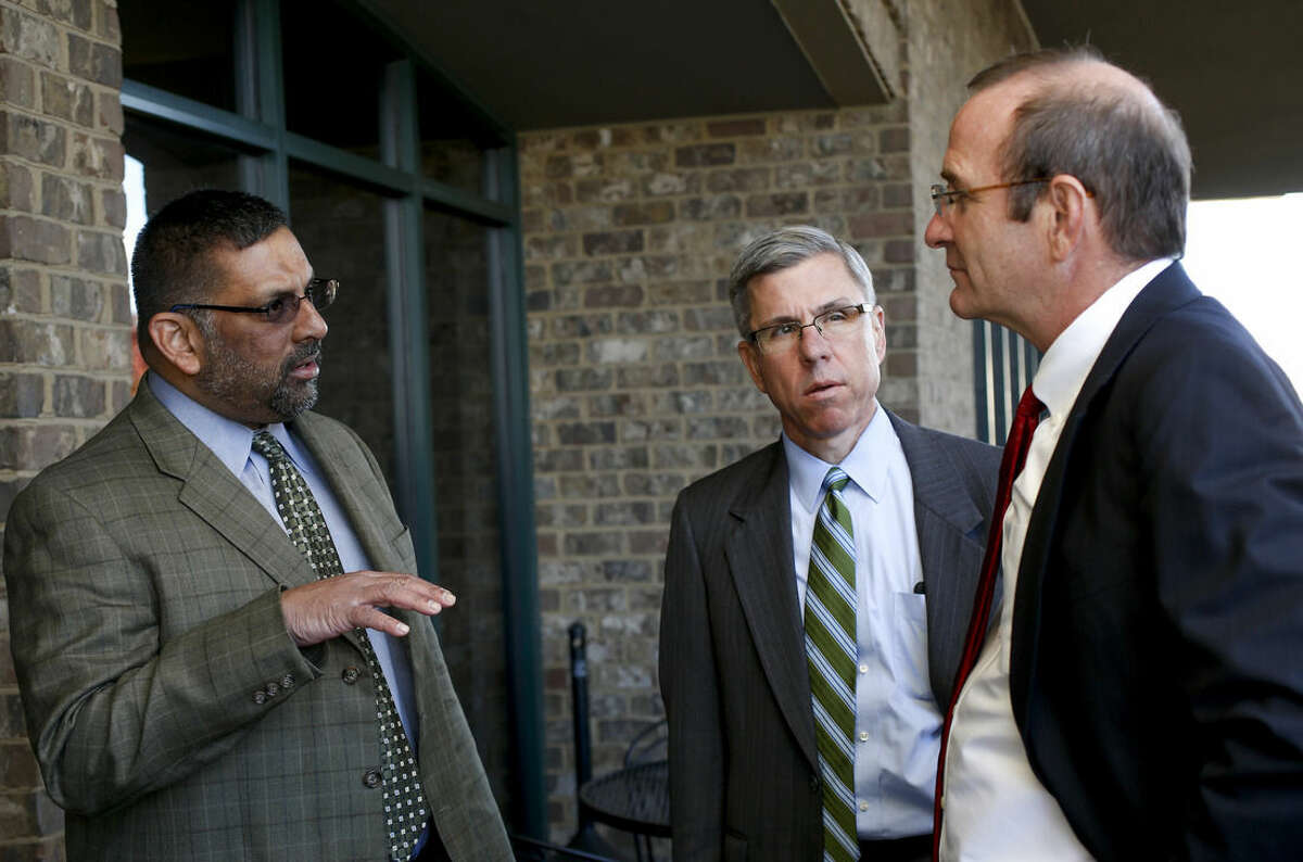 From left, David Wijewickrama, Scott Jones and Fred Barbour, attorneys representing North Carolina state troopers in a lawsuit over pay, discuss the case at their Asheville, N.C. office, Thursday, Nov. 19, 2015. State troopers suing North Carolina for millions of dollars in back pay say the state's broken promises have forced them into tough spots. It's not unusual for a trooper to have a second job and some are even on food stamps. (AP Photo/Nell Redmond)
