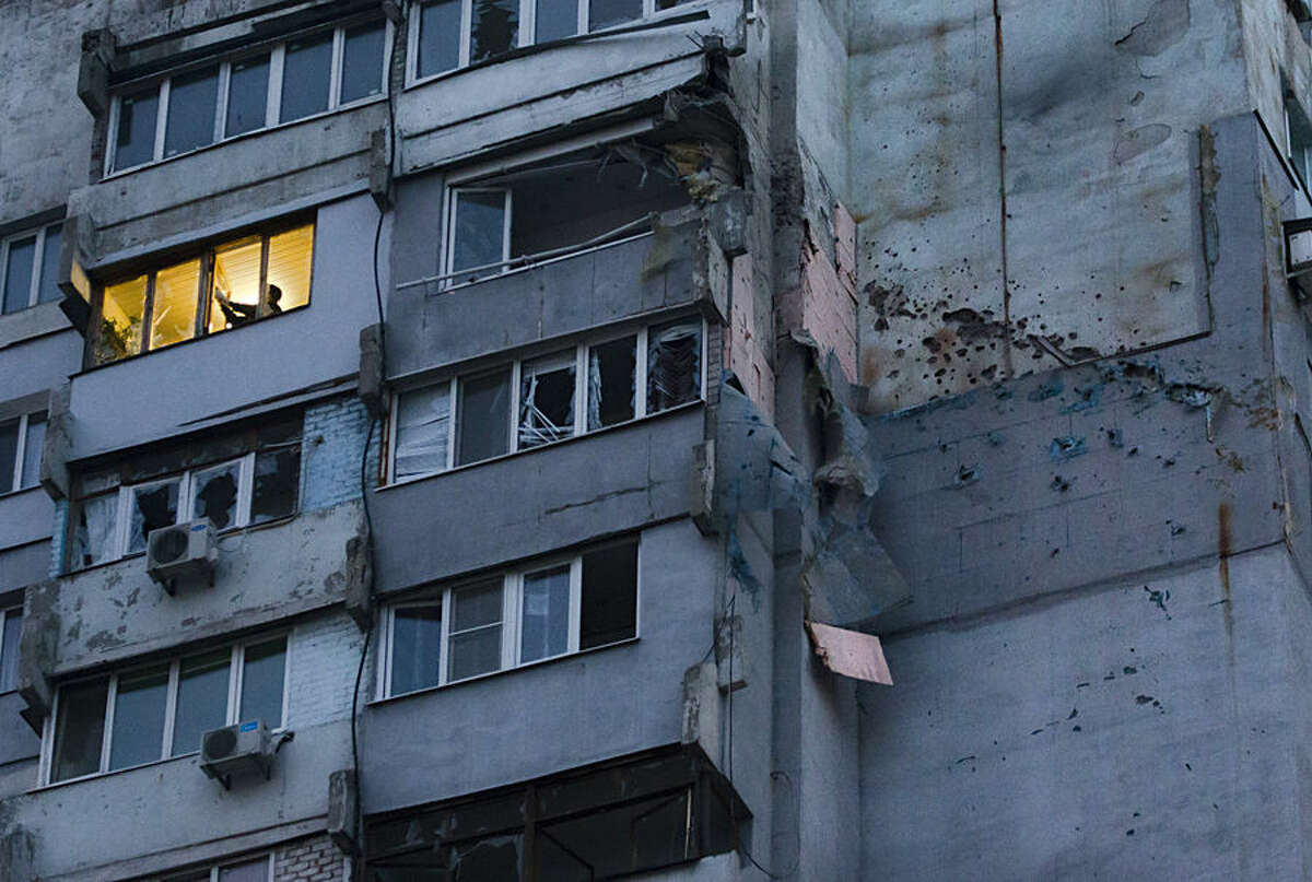 A man removes shattered glass from a broken window after shelling in the town of Donetsk, eastern Ukraine, Wednesday, Oct. 8, 2014. The United Nations says least 331 deaths have been reported in eastern Ukraine since last month's cease-fire deal between Russian-backed separatists and government troops. Hostilities continue in the main rebel-held city of Donetsk, as well as around two other towns. (AP Photo/Dmitry Lovetsky)