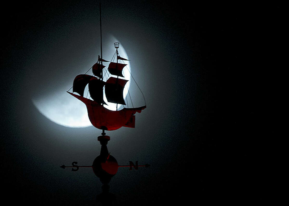 The Earth's shadow begins to fall over the moon during a total lunar eclipse, behind a weathervane shaped like a Spanish galleon on the Freedom Tower in Miami, Wednesday, Oct. 8, 2014. (AP Photo/Wilfredo Lee)