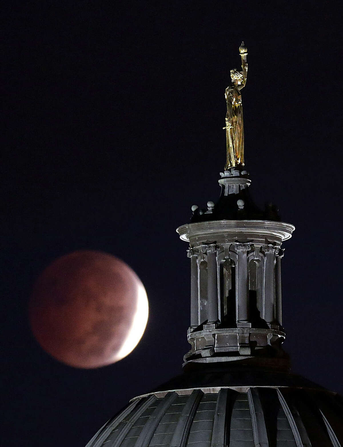 A lunar eclipse is seen near a statue entitled