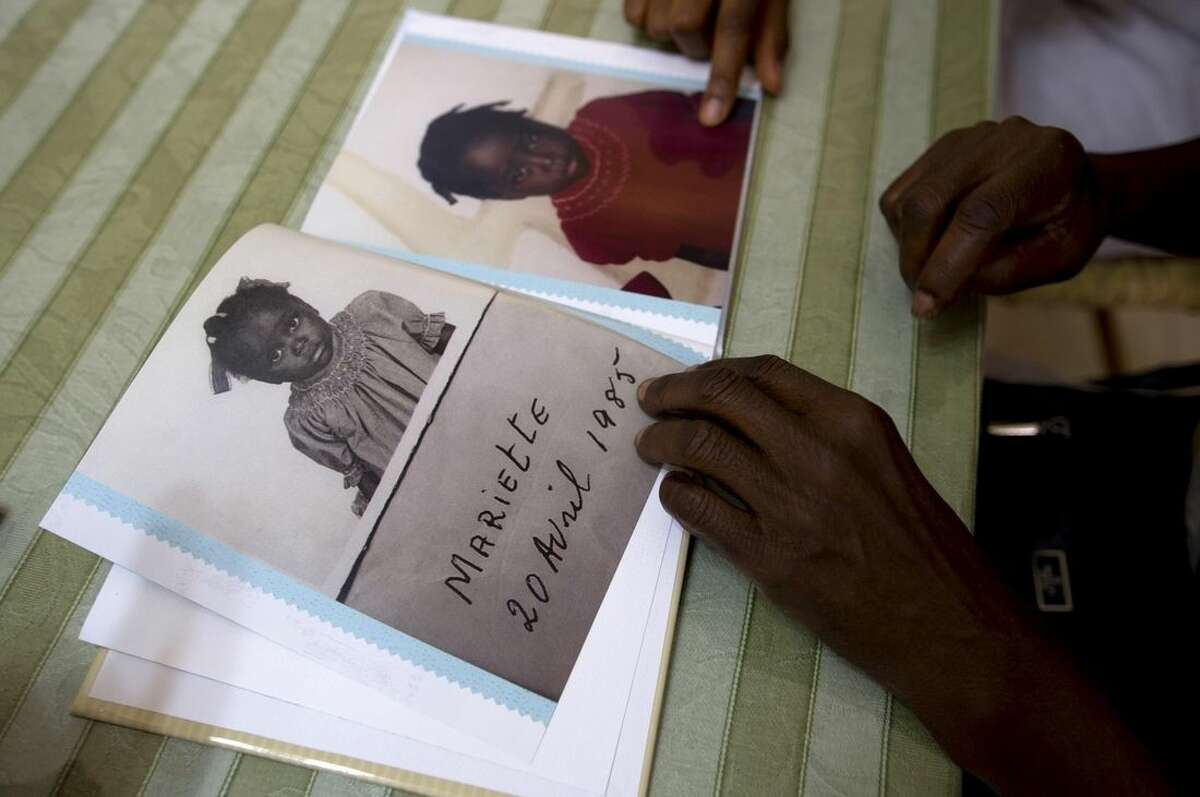 In this July 13, 2015 photo, during a visit with her birth mother and other family, in Port-au-Prince, Haiti, adoptee Mariette Williams shows pictures of herself, made when she was living at a Haitian orphanage in the mid 80's. For the first time in nearly 30 years, Mariette was reunited with her birth mother. Mariette was adopted by a Canadian couple in October 1986. (AP Photo/Dieu Nalio Chery)