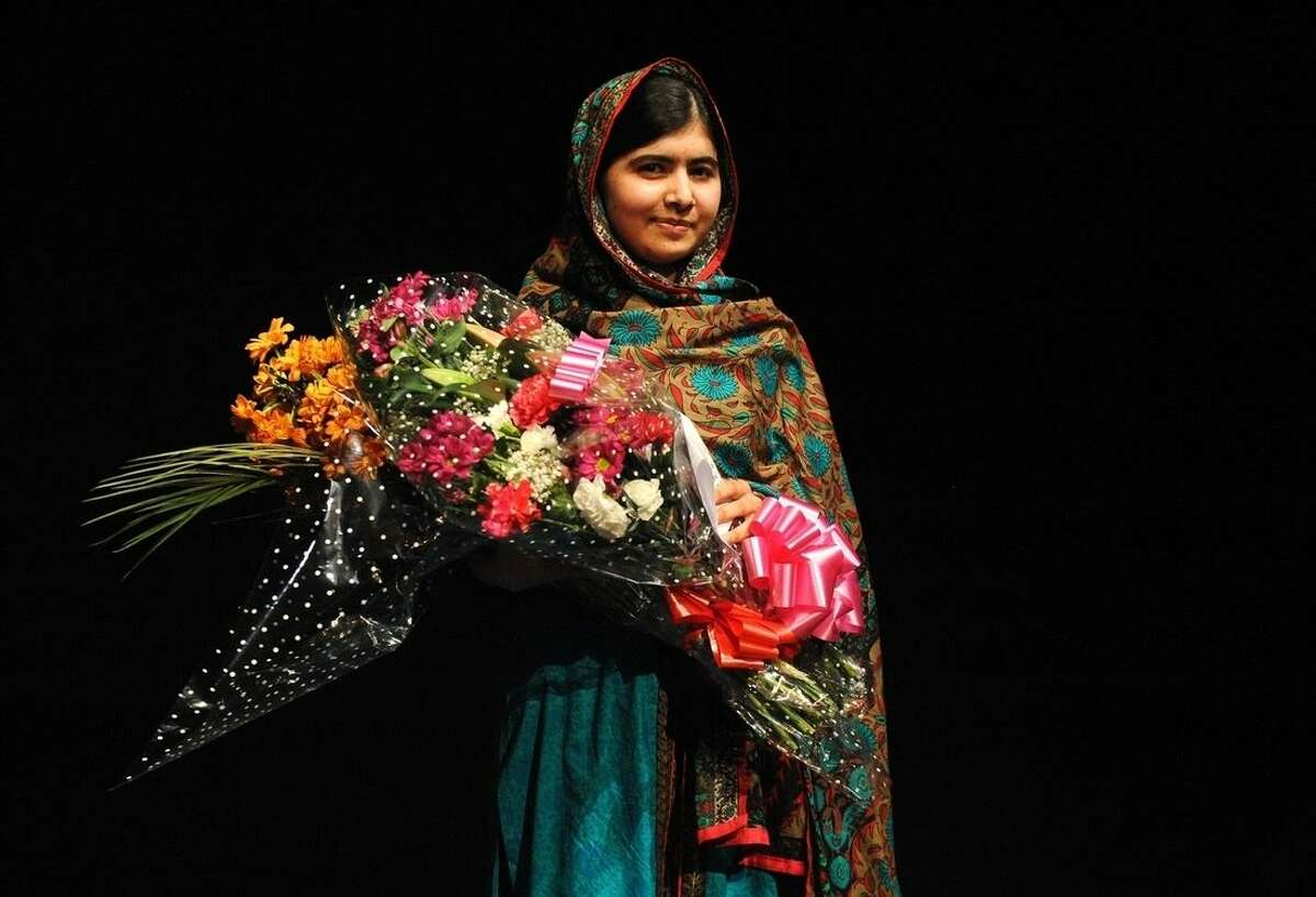 Malala Yousafzai poses with a bouquet after speaking during a media conference at the Library of Birmingham, in Birmingham, England, Friday, Oct. 10, 2014, after she was named as winner of The Nobel Peace Prize. The Nobel Peace Prize 2014, is awarded jointly to Malala Yousafzai of Pakistan and Kailash Satyarthi of India, for risking their lives to fight for children's rights. Malala was shot in the head by a Taliban gunman two-years ago in Pakistan for insisting that girls have the right to an education. (AP Photo/Rui Vieira)