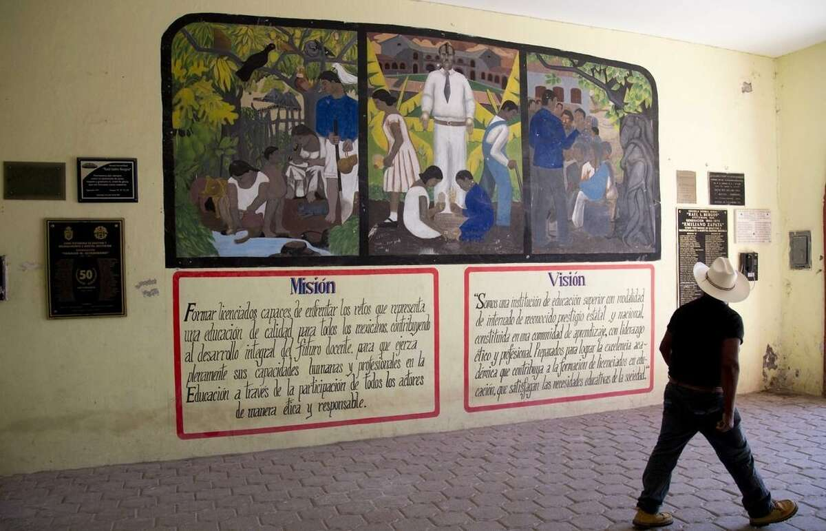 In this Oct. 6, 2014 photo, a man looks up at a mural inside the Raul Isidro Burgos rural teacher's college in Tixtla, Mexico. Two weeks after 43 students disappeared in a clash with police in southern rural Mexico, dozens of parents have gathered at the teacher's college also known as Ayotzinapa, that was supposed to be their sons' escape from life as subsistence farmers. (AP Photo/Eduardo Verdugo)