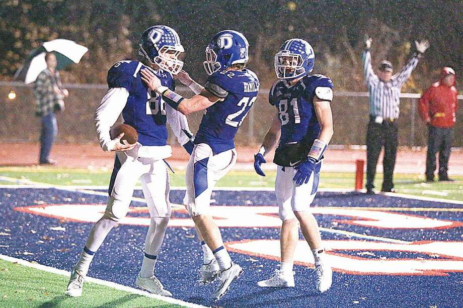 Hour photo/Chris Palermo. Darien players celebrate Spencer Jarecke's touchdown during Darien's 41-7 Class LL state tournament victory over Staples at Brien McMahon High School Tuesday night.
