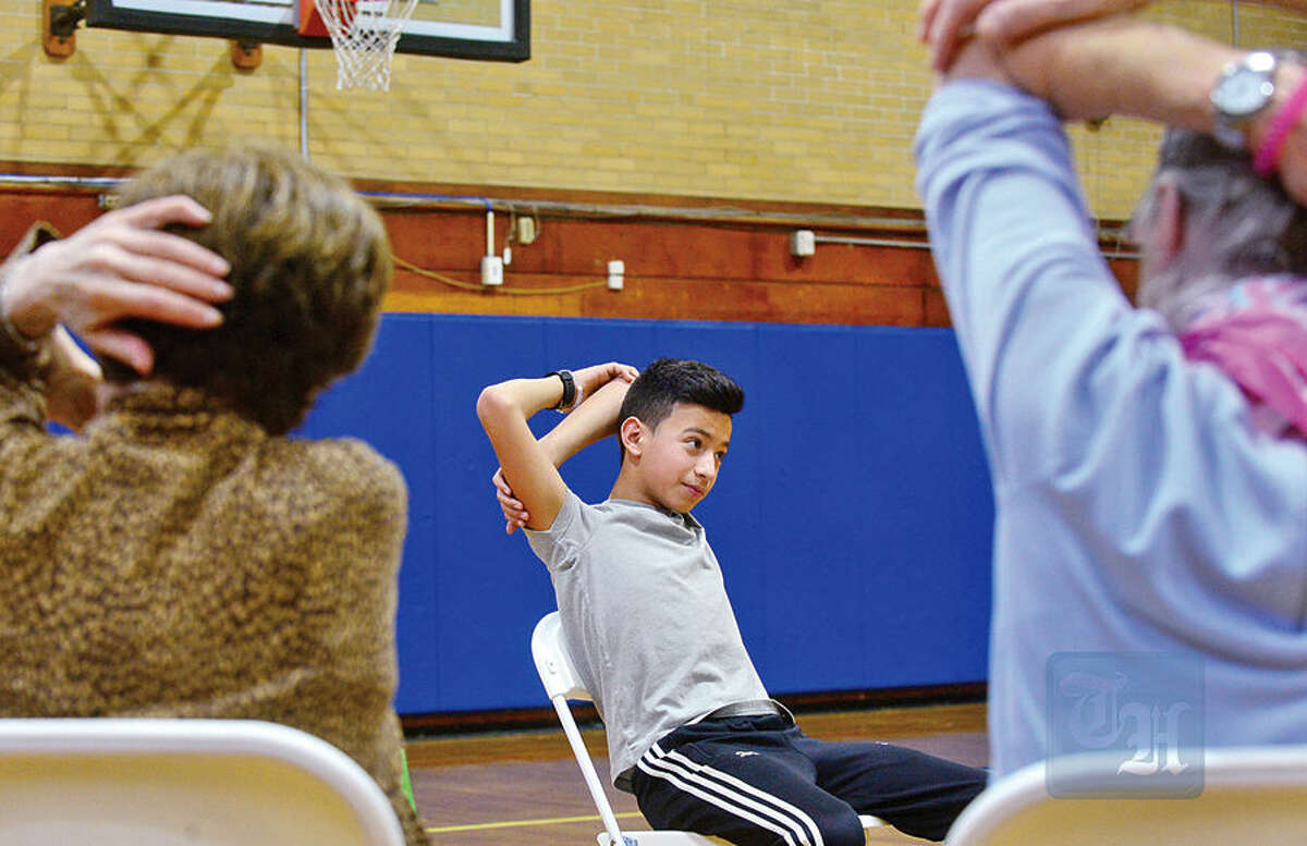 Hour photo / Erik Trautmann Residents for Maplewood Senior Housing take part in a chair aerobics program with Nathan Hale Middle School students including 7th grader Justin Blanco Wednesday at the school.