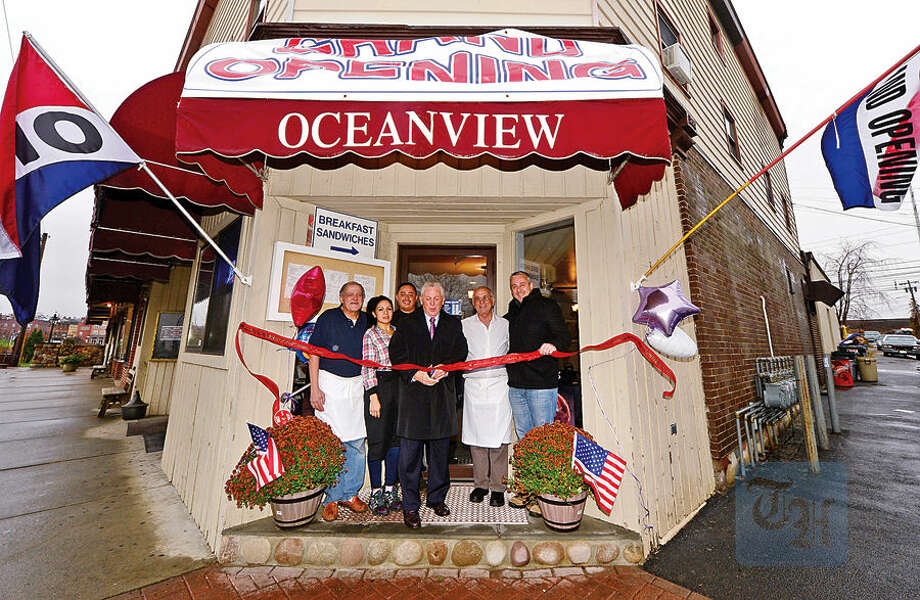 Hour photo / Erik Trautmann Norwalk mayor Harry Rilling cuts the ribbon for the reopening of the Oceanview Cafe at Liberty Square as Oceanview staff, Magdi Elawadi, Paula Gonzalez, Frank Henriquez, John Kaipides and Councilman John Kydes look on Wednesday.