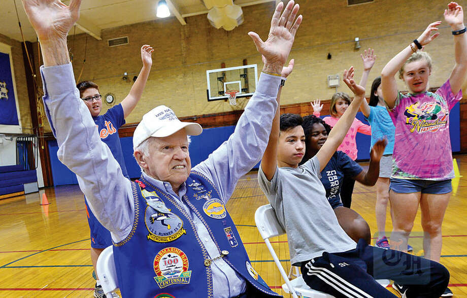 Hour photo / Erik Trautmann Residents for Maplewood Senior Housing including George Pltia take part in a chair aerobics program with Nathan Hale Middle School students Wednesday at the school.