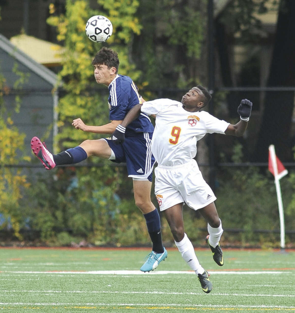 Hour photo/John Nash Weston's Frank Lugossy, left, heads the ball before it gets to Stratford's Anthony Afiyei during Saturday's boys soccer game at Penders Field in Stratford. Weston won 3-1.