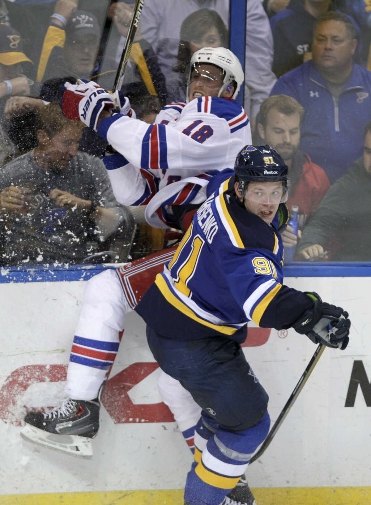 St. Louis Blues' Vladimir Tarasenko (91) slams New York Rangers' Marc Staal (18) into the boards in the third period of a NHL hockey game, Thursday, Oct. 9, 2014 in St. Louis. The Rangers beat the Blues 3-2. (AP Photo/Tom Gannam)