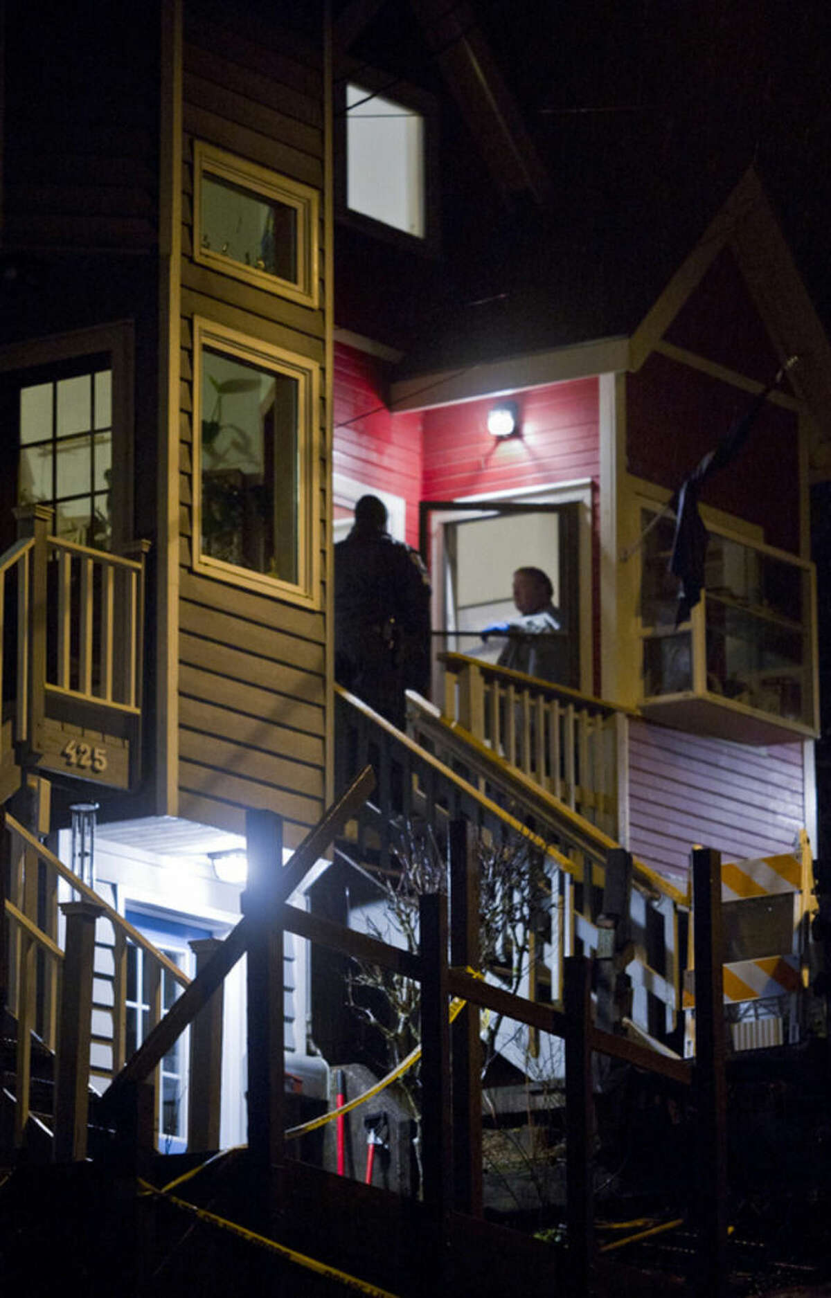 In this photo taken Monday night, Nov. 30, 2015, Juneau Police Chief Bryce Johnson talks with detectives at the front door of Mayor Stephen