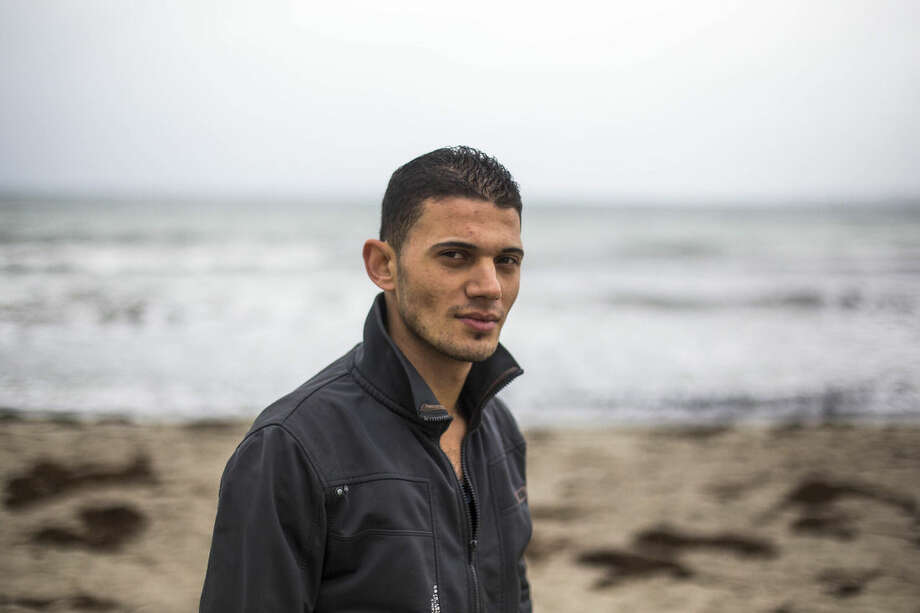 In this picture taken Monday, Sept. 22, 2014, Syrian refugee Mohammad Suleimane walks over the beach at the district Travemuende of north German city Luebeck. The young barber from Damascus was the only one of 13 family members to survive when his boat sank, killing more than 200 refugees a year ago Saturday, an anniversary that comes as Europe faces a new wave of migrants making the perilous crossing from North Africa to the Italian island of Lampedusa. (AP Photo/Markus Schreiber)