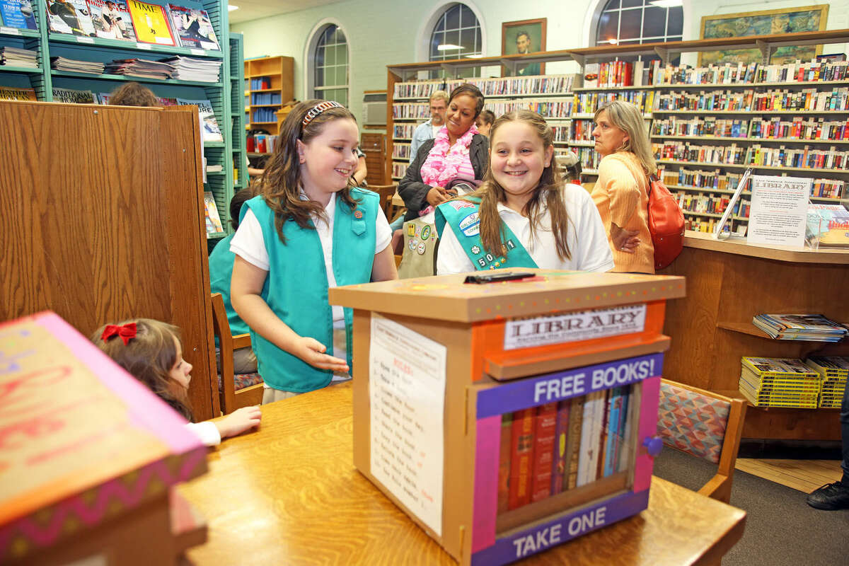 Girl Scouts Lilliana Soto, 10 and Toni Horton, 11 show off the book nook they made at the East Norwalk Library Friday evening. As part of its