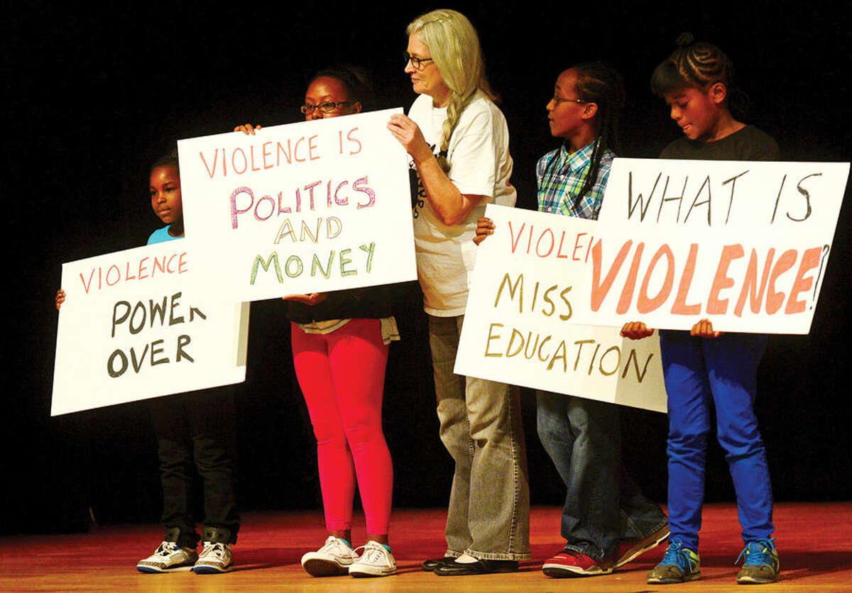 Hour photo / Erik Trautmann Judy Meikle of the Youth Council for Justice, center, gets help displaying the groups message as Serving All Vessels Equally, Inc., (SAVE) convenes the first CT Stomp the Violence Conference Saturday at West Rocks School. The conference seeks to foster a regional conversation about youth and gang violence and raise awareness about the problem. The Conference also seeks to enable local communities to more effectively address youth violence through comprehensive planning and the sharing of common challenges and strategies.