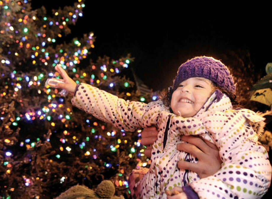 Three year old Kimberly Tejava gets a lift for closer look as Stew Leonard's Christmas tree lights up Tuesday for the annual tree lighting celebration in Norwalk.Hour photo/Matthew Vinci