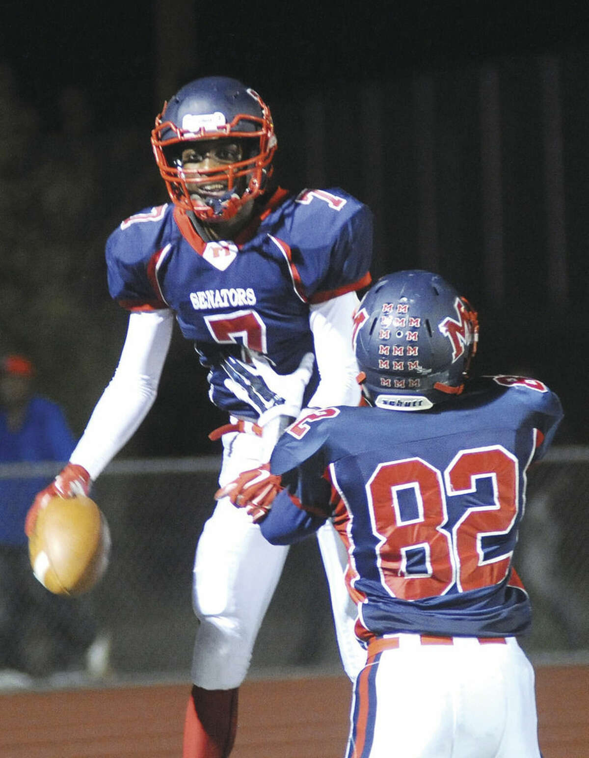 Hour photo/John Nash McMahon's Kentrell Snider (7) jumps into the arms of teammate David Daniel after catching an 18-yard touchdown pass on Friday against Harding.