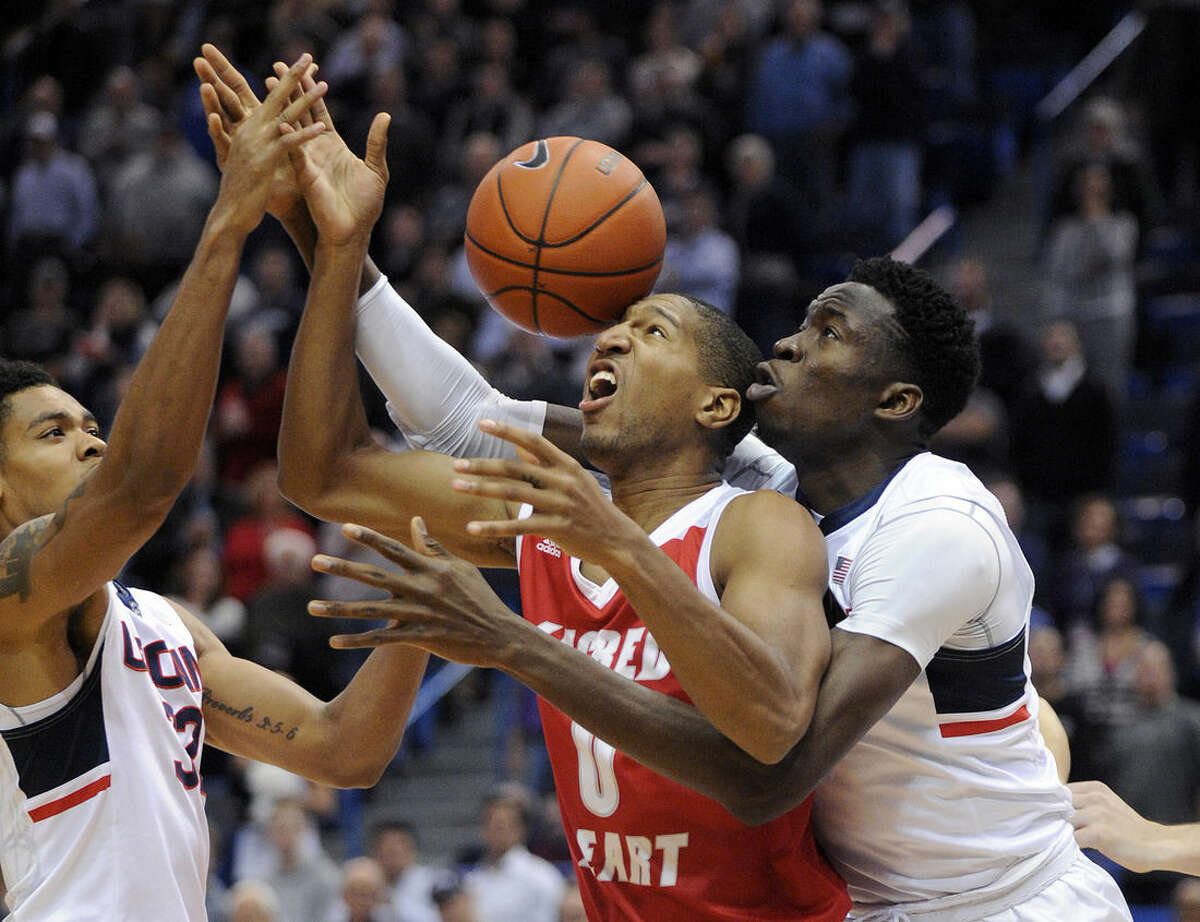 Sacred Heart's Jordan Allen (0) vies for the ball with Connecticut's Shonn Miller, left, and Amida Brimah during the first half of an NCAA college basketball game in Hartford, Conn., on Wednesday, Dec. 2, 2015. (AP Photo/Fred Beckham)