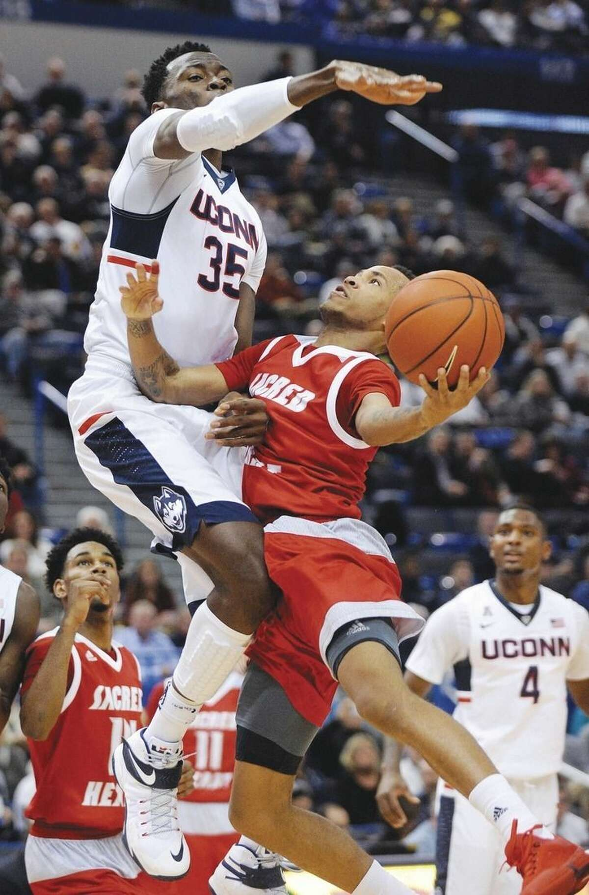 Connecticut's Amida Brimah (35) guards Sacred Heart's Cane Broome during the first half of an NCAA college basketball game in Hartford, Conn., Wednesday, Dec. 2, 2015. (AP Photo/Fred Beckham)