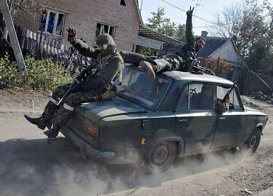 FOR USE AS DESIRED, YEAR END PHOTOS - FILE - Pro-Russian rebels ride atop a car to their positions not far from the Donetsk Sergey Prokofiev International Airport in the city of Donetsk, eastern Ukraine, Tuesday, Oct. 14, 2014. (AP Photo/Dmitry Lovetsky, File)