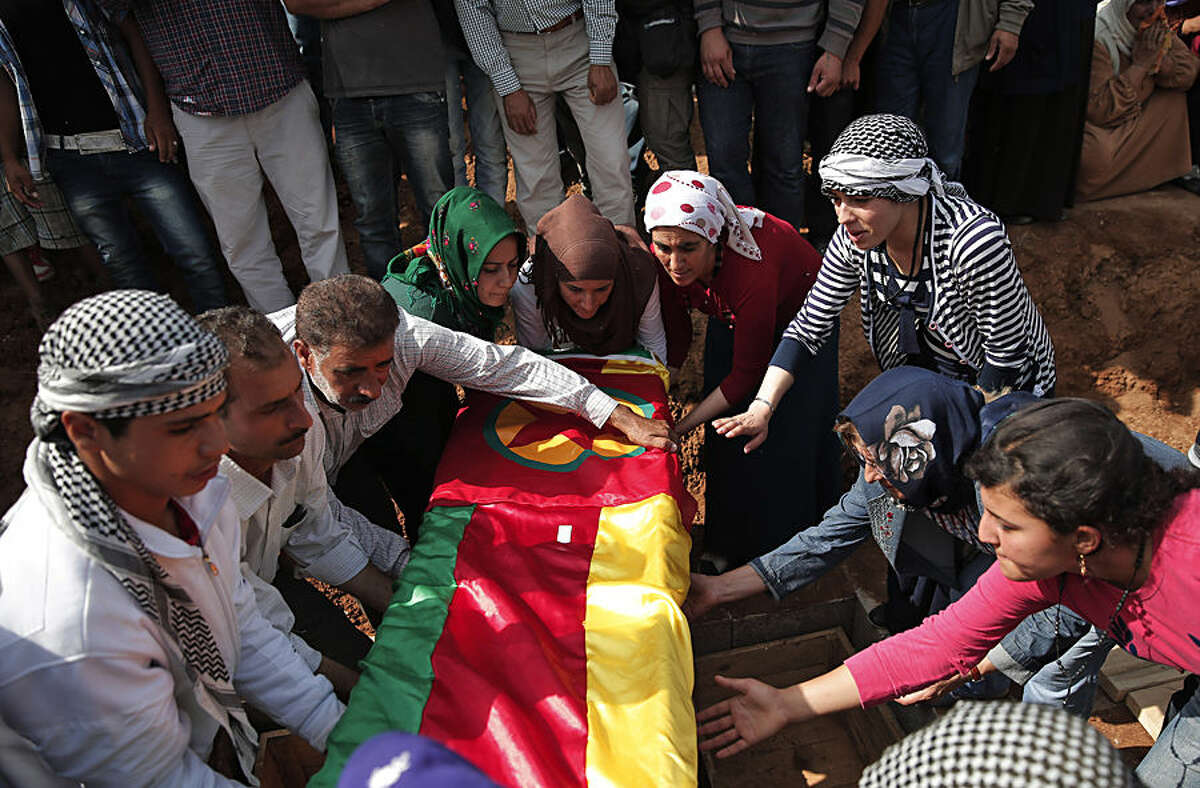 Mourners lower the coffin bearing the body of Mizgin Culbakge, a female Kurdish fighter killed in clashes with militants of the Islamic State group in Kobani, Syria, during the funeral of four female fighters, at a cemetery in Suruc, on the Turkey-Syria border, Tuesday, Oct. 14, 2014. Kobani, also known as Ayn Arab, and its surrounding areas, has been under assault by extremists of the Islamic State group since mid-September and is being defended by Kurdish fighters. (AP Photo/Lefteris Pitarakis)