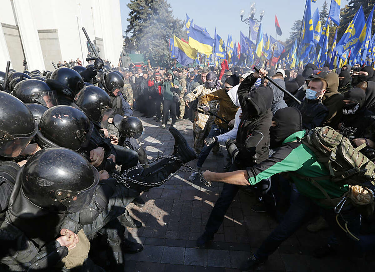 Police clash with demonstrators outside parliament in Kiev, Ukraine, on Tuesday, Oct. 14, 2014, as deputies repeatedly voted down proposals to officially recognize a contentious WWII-era partisan group as national heroes. Thousands of Svoboda nationalist party supporters rallied in Kiev earlier in the day in celebration of the Ukrainian Insurgent Army, but officials from the party denied vehemently that its members were involved in the unrest.(AP Photo/Sergei Chuzavkov)