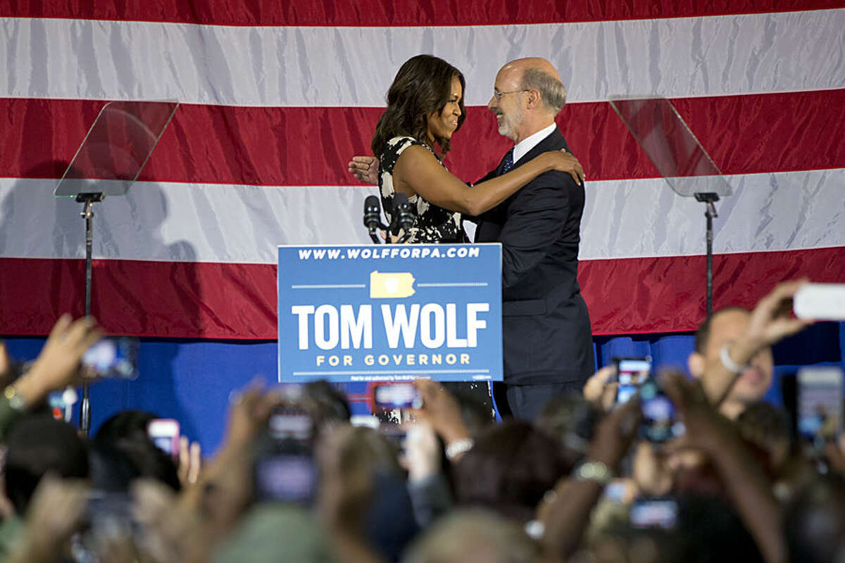 First lady Michelle Obama hugs Pennsylvania Democratic gubernatorial candidate Tom Wolf Wednesday, Oct. 15, 2014, as she campaigns for him at the Dorothy Emanuel Recreation Center in Philadelphia. (AP Photo/Matt Rourke)