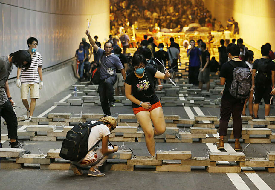Demonstrators block the underpass with concrete slabs taken from drainage ditches at the main roads outside government headquarters in Hong Kong's Admiralty, Wednesday, Oct. 15, 2014. Pro-democracy activists clashed with police and barricaded a tunnel near Hong Kong's government headquarters late Tuesday, expanding their protest zone again after being cleared out of some other streets in the latest escalation of tensions in a weeks long political crisis. (AP Photo/Kin Cheung)