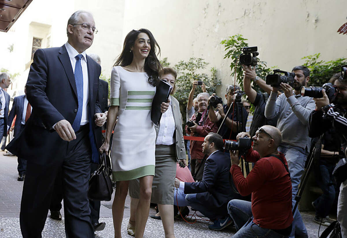 Members of the media take photographs of Greek Culture Minister Kostas Tassoulas, left, and lawyer Amal Clooney, after their meeting, in Athens, Tuesday, Oct. 14, 2014. Lawyers Geoffrey Robertson and Amal Clooney arrived Monday on a four-day visit to meet government officials, including Prime Minister Antonis Samaras, and advise on Greece's quest to have the Parthenon Marbles returned to Athens. (AP Photo/Thanassis Stavrakis)