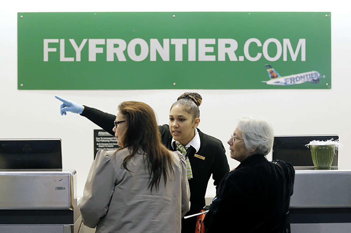 A Frontier Airlines employee wears gloves as she directs passengers where to go at Cleveland Hopkins International Airport Wednesday, Oct. 15, 2014, in Cleveland. Ohio health officials aren't sure how many people came into contact with a Texas nurse as she visited family in the Akron area days before being diagnosed with Ebola in Dallas. The Ohio Department of Health says she visited family from Oct. 8-13 and flew Monday from Cleveland to Dallas. (AP Photo/Tony Dejak)
