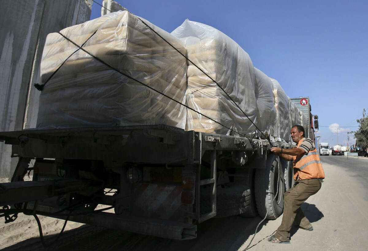 A Palestinian worker checks a truck loaded with sacks of cement at the Kerem Shalom border crossing on its way from Israel to Rafah in the southern Gaza Strip,Tuesday, Oct. 14, 2014. U.N. chief Ban Ki-moon visited the Gaza Strip on Tuesday to give a push to international reconstruction efforts following a devastating summertime war, saying the vast scenes of destruction were