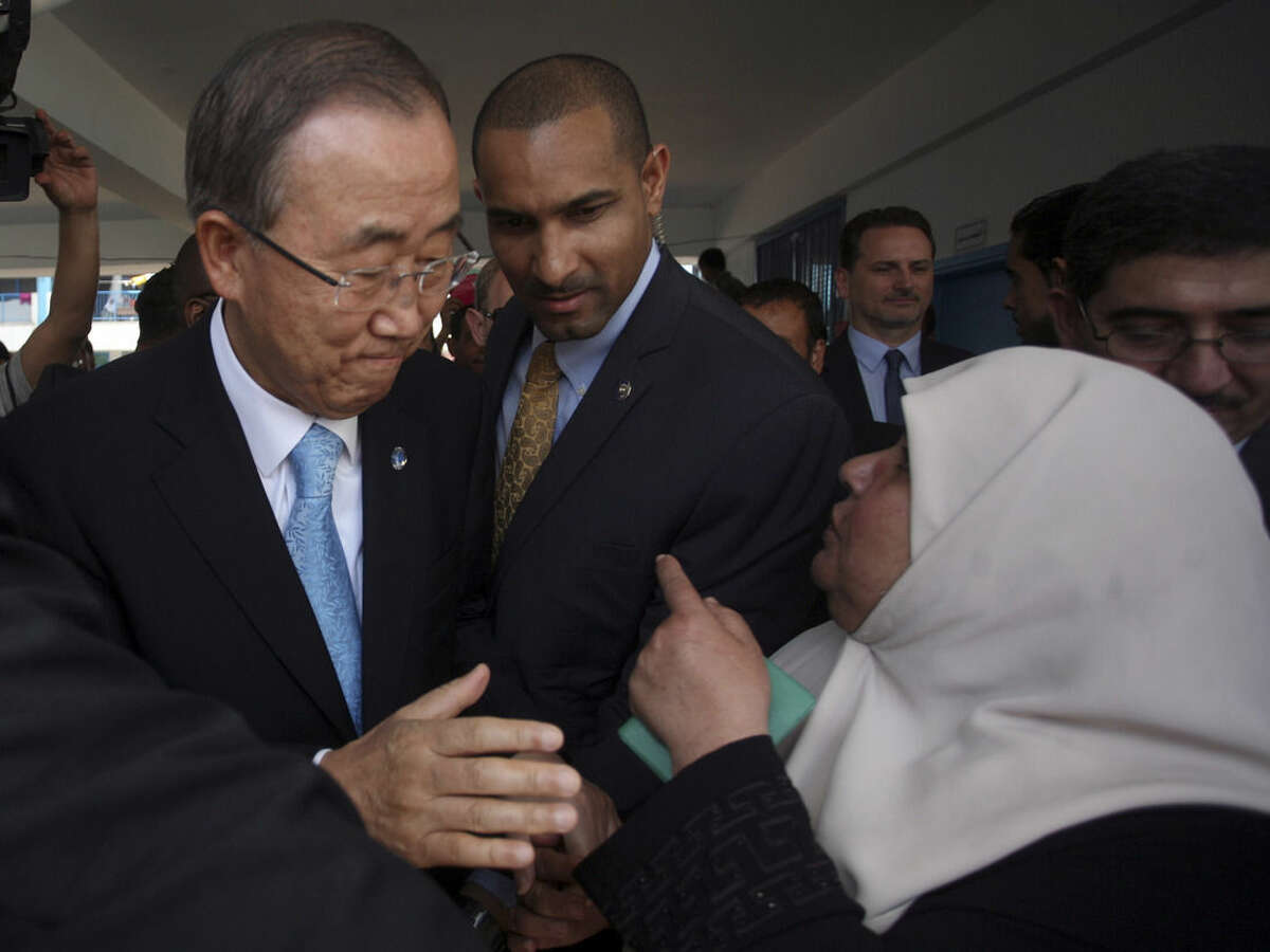 United Nations Secretary-General Ban Ki-moon speaks to a Palestinian woman in Gaza Tuesday, Oct. 14, 2014. During the visit to Gaza Strip the U.N. chief said the destruction he saw in Gaza was