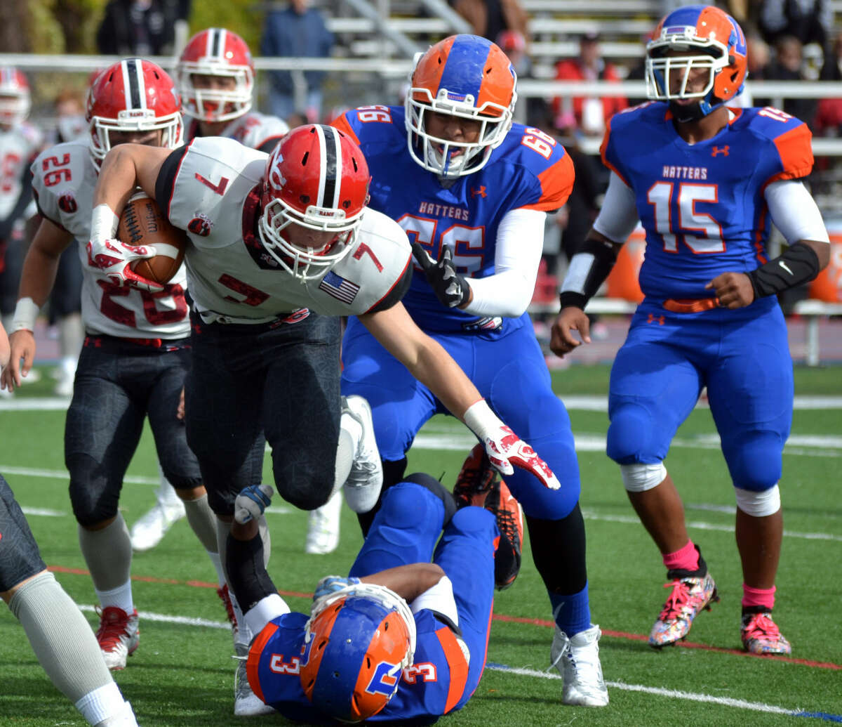 New Canaan's Ryan O'Connell runs over a Danbury defender on October 17, 2015. (Pete Paguaga/Hour photo)