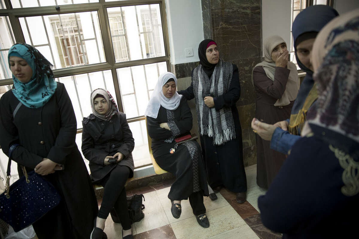 The mother of Mohammed Abu Khdeir, center, sits after the reading of the verdict in his killing, at the Jerusalem District Court, Monday, Nov. 30, 2015. The Jerusalem court on Monday convicted two Israeli youths in the grisly killing of Abu Khdeir, while delaying a verdict for 31-year-old Yosef Haim Ben David in the case due to a last-minute insanity plea. In Monday's ruling, Judge Jacob Zaban determined that Ben David, and two Israeli minors had snatched Abu Khdeir from an east Jerusalem sidewalk in July 2014 and burned him alive in a forest outside the city. (AP Photo/Oded Balilty)