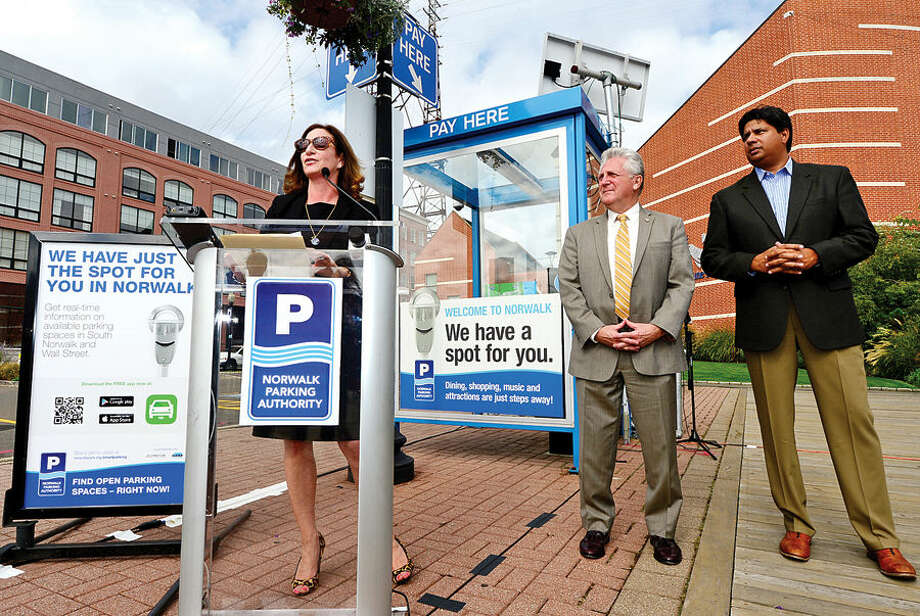 Hour photo / Erik Trautmann Norwalk Parking Authority Administraive Services Manager Kathryn Hebert speaks during a press conference at the North Water St lot Tuesday as the Authority announces a new digital initiative that allows access to parking availability information with the smart phone application, Parker. The system works via wireless sensors that are embedded in parking space to detect whether or not the space is occupied. Data from each sensor is relayed via wireless to the cloud and pushed into an easy-to-use app showing real-time parking availability. CASE parking, a parking data solutions provider, will collect occupancy data from the lots and garages. Streetline, the leading global provider of sensor-based smart parking technology, has outfitted the on-street parking spaces with sensors. The data from both systems will be streamed directly into Streetline's mobile app, Parker.