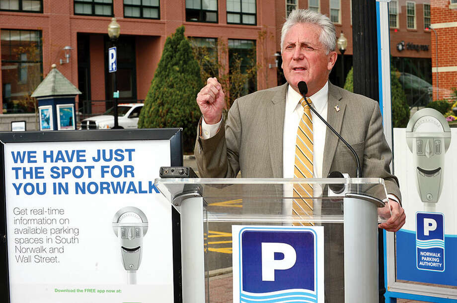 Hour photo / Erik Trautmann Norwalk mayor Harry Rilling speaks during a press conference at the North Water St lot Tuesday as the Norwalk Parking Authority announces a new digital initiative that allows access to parking availability information with the smart phone application, Parker. The system works via wireless sensors that are embedded in parking space to detect whether or not the space is occupied. Data from each sensor is relayed via wireless to the cloud and pushed into an easy-to-use app showing real-time parking availability. CASE parking, a parking data solutions provider, will collect occupancy data from the lots and garages. Streetline, the leading global provider of sensor-based smart parking technology, has outfitted the on-street parking spaces with sensors. The data from both systems will be streamed directly into Streetline's mobile app, Parker.