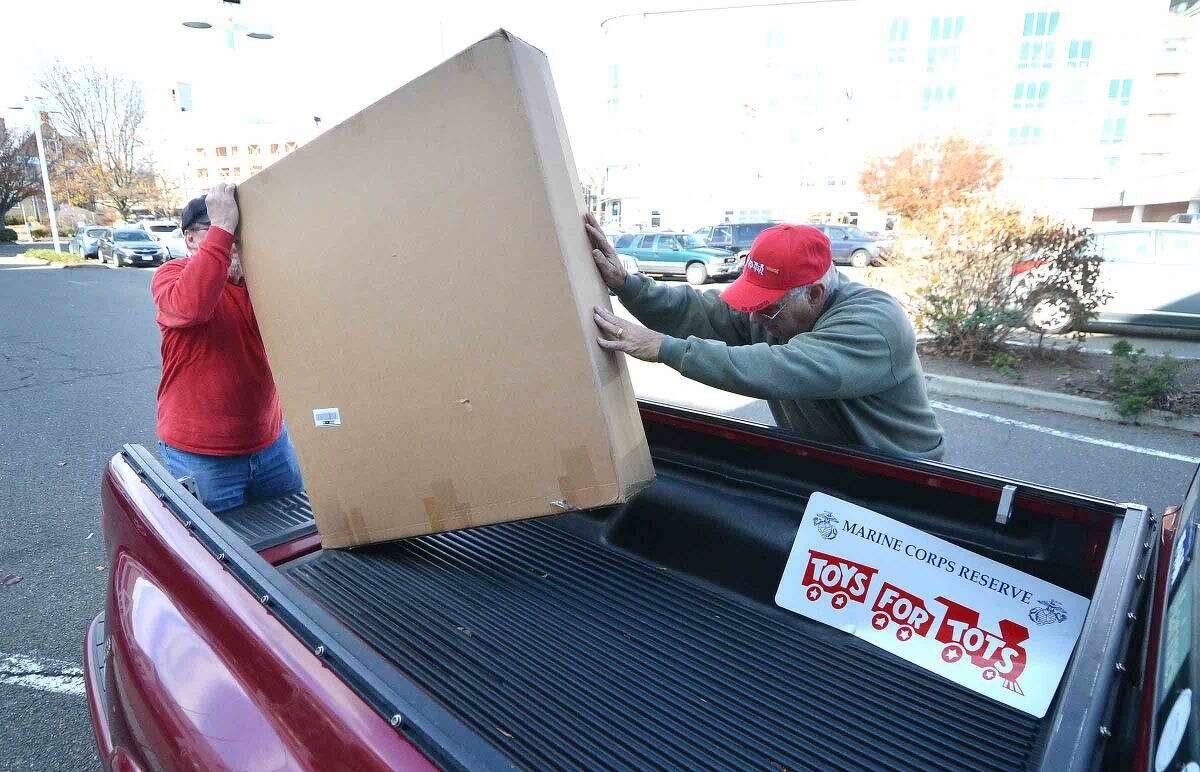 Hour Photo/Alex von Kleydorff Volunteers Peter Havens and Dan Caporale unload boxes of collection boxes to be placed at various Toys for Tots Collection sites in Norwalk, Westport, Fairfield and parts of Wilton
