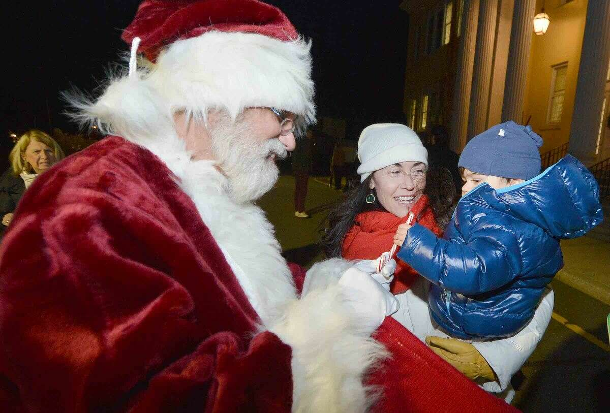 Hour Photo/Alex von Kleydorff 1.5 yr old Cole Shambroom gets a candy cane from Santa with mom Jenneifer during the Westport Christmas Tree lighting at Town Hall