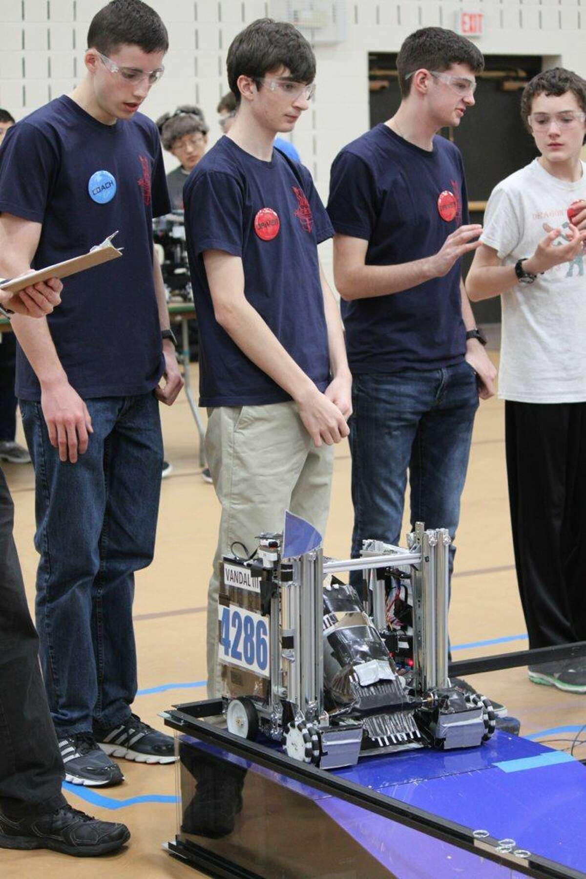 From left to right: Ryan Petschek, Tyler Green and Scott Barnet, members of Dragonoids team, prepare while a member of the Dragon Terminators team looks on.