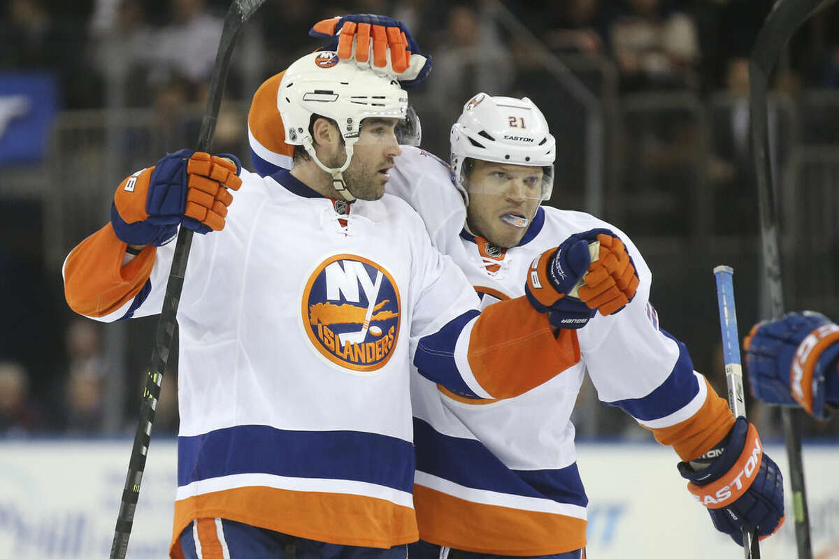 New York Islanders defenseman Johnny Boychuk, left, of celebrates with right wing Kyle Okposo (21) after scoring against New York Rangers goalie Henrik Lundqvist during the first period of an NHL hockey game at Madison Square Garden, Tuesday, Oct. 14, 2014, in New York. (AP Photo/John Minchillo)