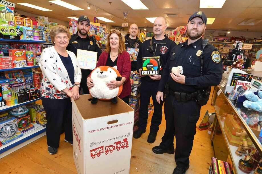 "From left to right: Toy Chest manager Bonnie McCarthy, Wilton police Officer Eric Patenaude, Toy Chest Owner Ann Lathrop,, Wilton firefighters Don Scarpetti and Mike Pryor and Wilton police Officer Shawn Frendt, are collecting toys at Wilton's ""Stuff a Cruiser"" event this Sunday."
