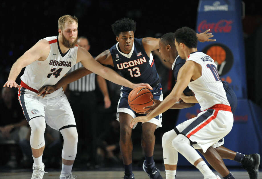Gonzaga center Przemek Karnowski (24), left and Connecticut forward Steven Enoch (13) look on as Connecticut guard Sterling Gibbs (4) scoops up a loose ball in front of Gonzaga guard Bryan Alberts (10) during the second half of an NCAA college basketball game, Friday, Nov. 27, 2015 in Paradise Island, Bahamas. (Brad Horrigan/Hartford Courant via AP) MANDATORY CREDIT