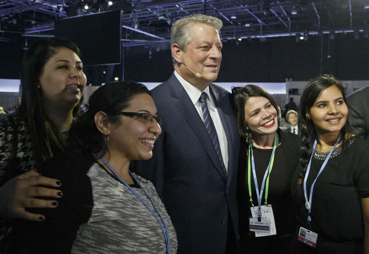 Former US Vice President Al Gore poses for a photo with delegates during the
