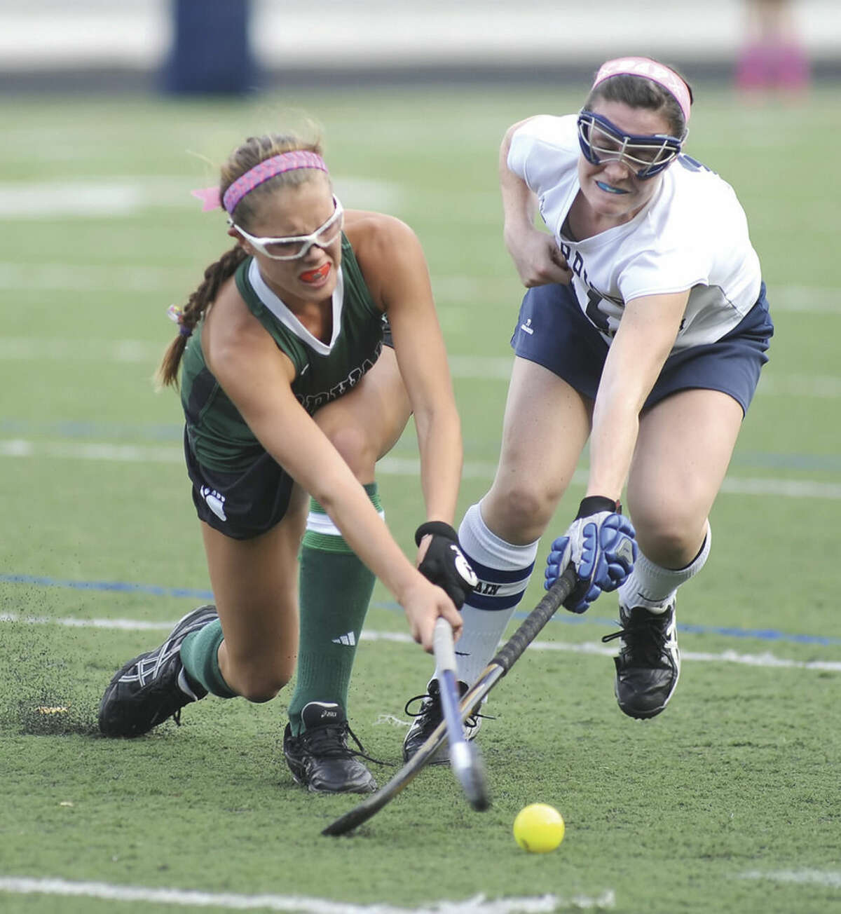 Hour photo/John Nash Norwalk's Samantha Bartush, left, and Wilton's Megan Cunningham fight for possession during Tuesday's FCIAC field hockey game at Fujitani Field in Wilton. The host Warriors came from behind to post a 2-1 win.