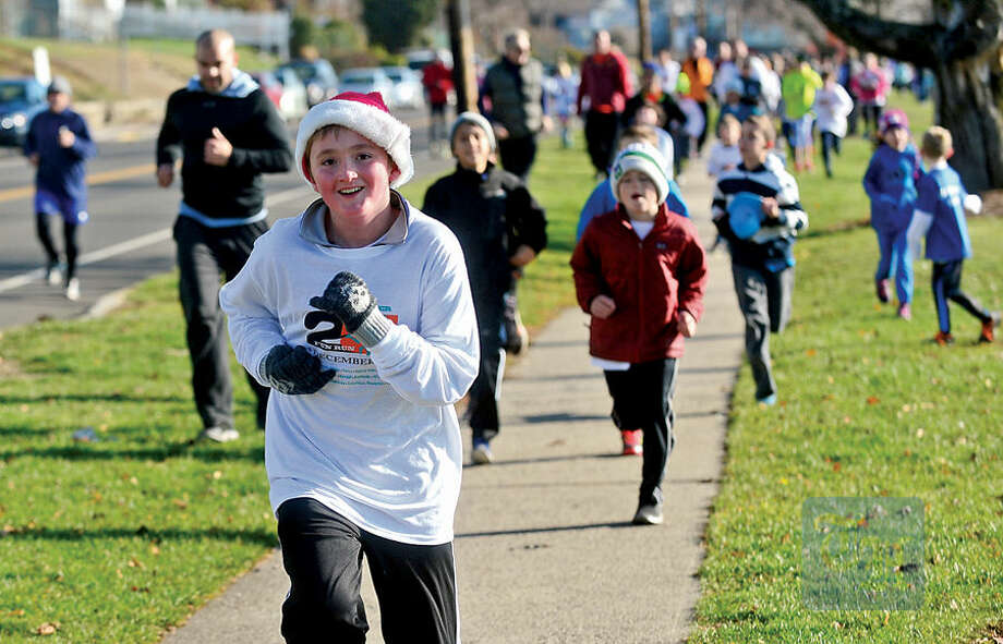 Hour photo / Erik Trautmann Local residents participate in the 1.2 mile 25th annual Norwalk River Fun Run at Veteran's Memorial Park in Norwalk Saturday.