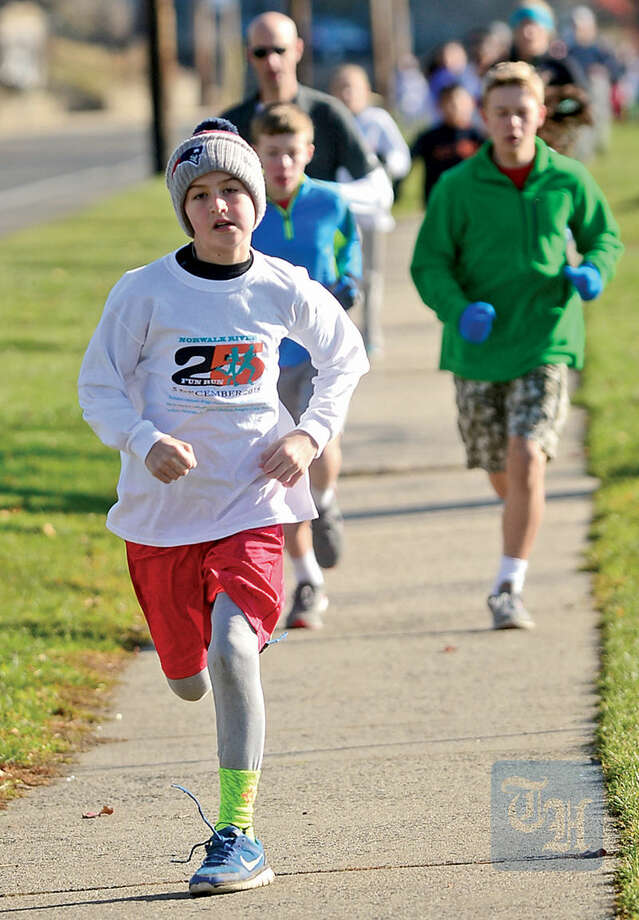 Hour photo / Erik Trautmann Local residents including Francis Norris-Loiva participate in the 1.2 mile 25th annual Norwalk River Fun Run at Veteran's Memorial Park in Norwalk Saturday.