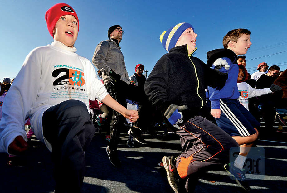 Hour photo / Erik Trautmann Zach DeVito and his friends warm up for the 1.2 mile 25th annual Norwalk River Fun Run at Veteran's Memorial Park in Norwalk Saturday.