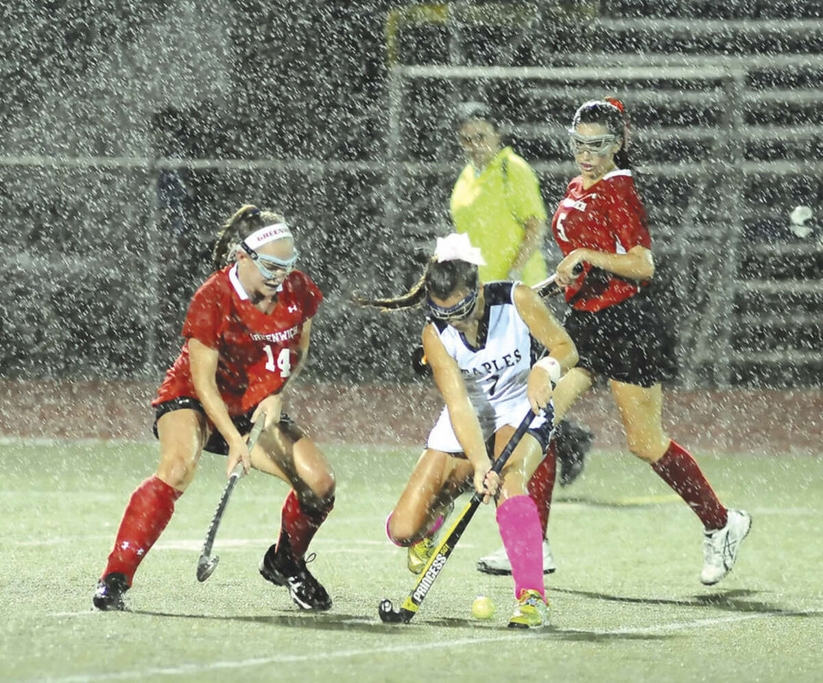 Hour photo/John Nash Staples' Meg Fay, center, plays the ball between Greenwich defenders Anne Dunster, left, and Kate Palastro, right, during Wednesday's game in Westport.