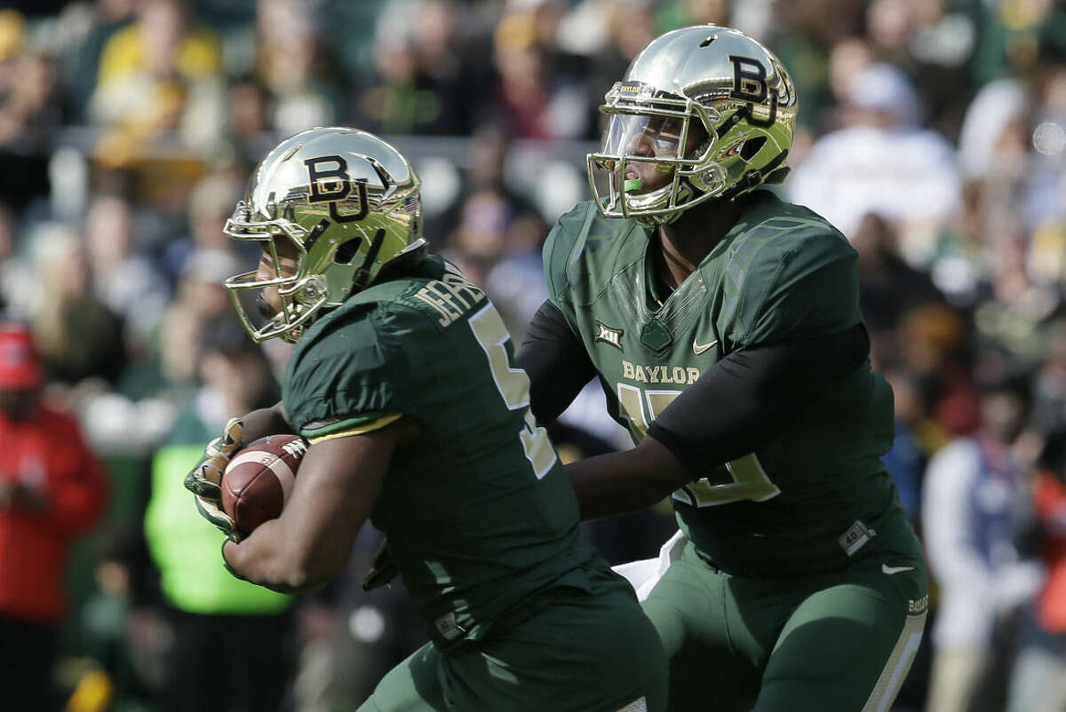 Baylor quarterback Chris Johnson (13) hands off to running back Johnny Jefferson (5) during the first half of an NCAA college football game against Texas Saturday, Dec. 5, 2015, in Waco, Texas. (AP Photo/LM Otero)