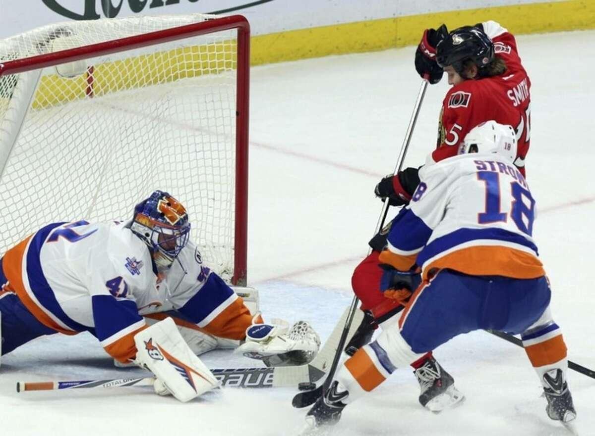 New York Islanders goalie Jaroslav Halak maks a stick save on Ottawa Senators' Zack Smith (15) a Islanders' Ryan Strome defends during first period NHL action in Ottawa, Saturday, Dec. 5, 2015. (Fred Chartrand/The Canadian Press via AP)