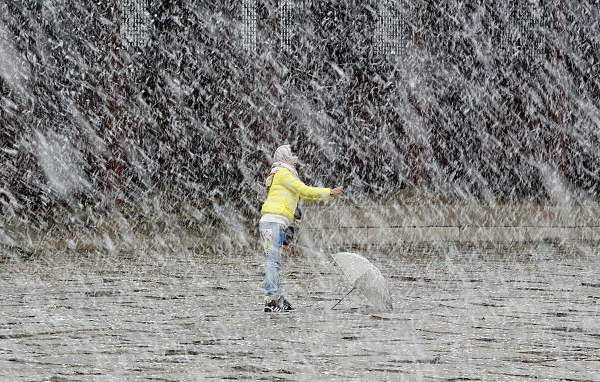 A visitor takes a selfie in heavy snow at the 14th-century Gyeongbok Palace, one of South Korea's well known landmarks in Seoul, South Korea, Thursday, Dec. 3, 2015. South Korean Meteorological Administration issued a heavy snowfall watch for Seoul and some other cities. (AP Photo/Lee Jin-man)